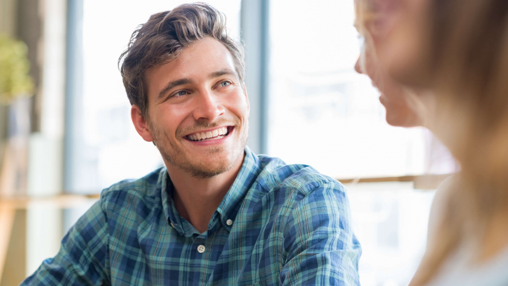 Closeup of cheerful young man in conversation with woman in cafeteria. Happy young couple talking and smiling sitting at table. Handsome guy smiling with his friends.