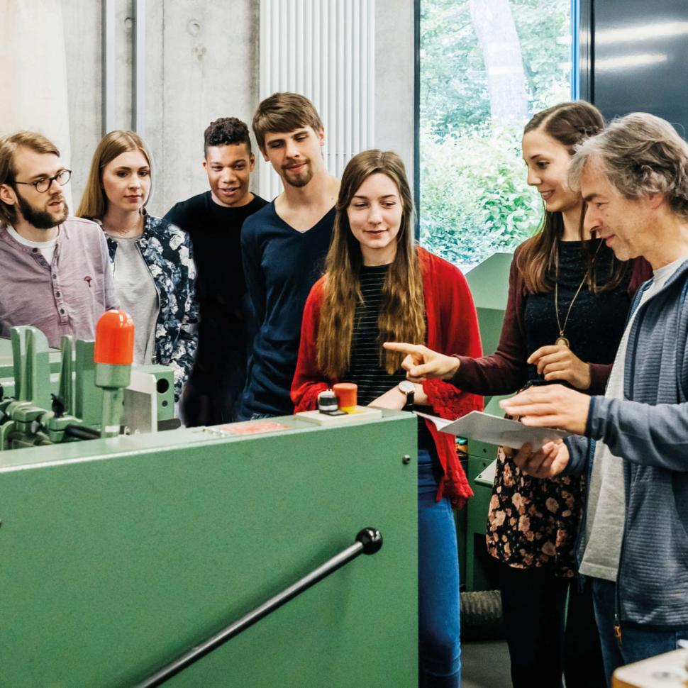 A group of university students learning about some industrial print machinery with the tutor.