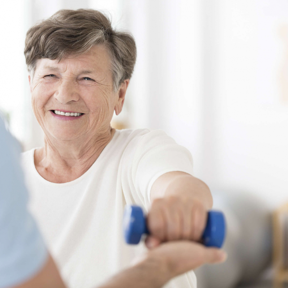 Happy senior woman exercising arms with small weights with help from a physiotherapist