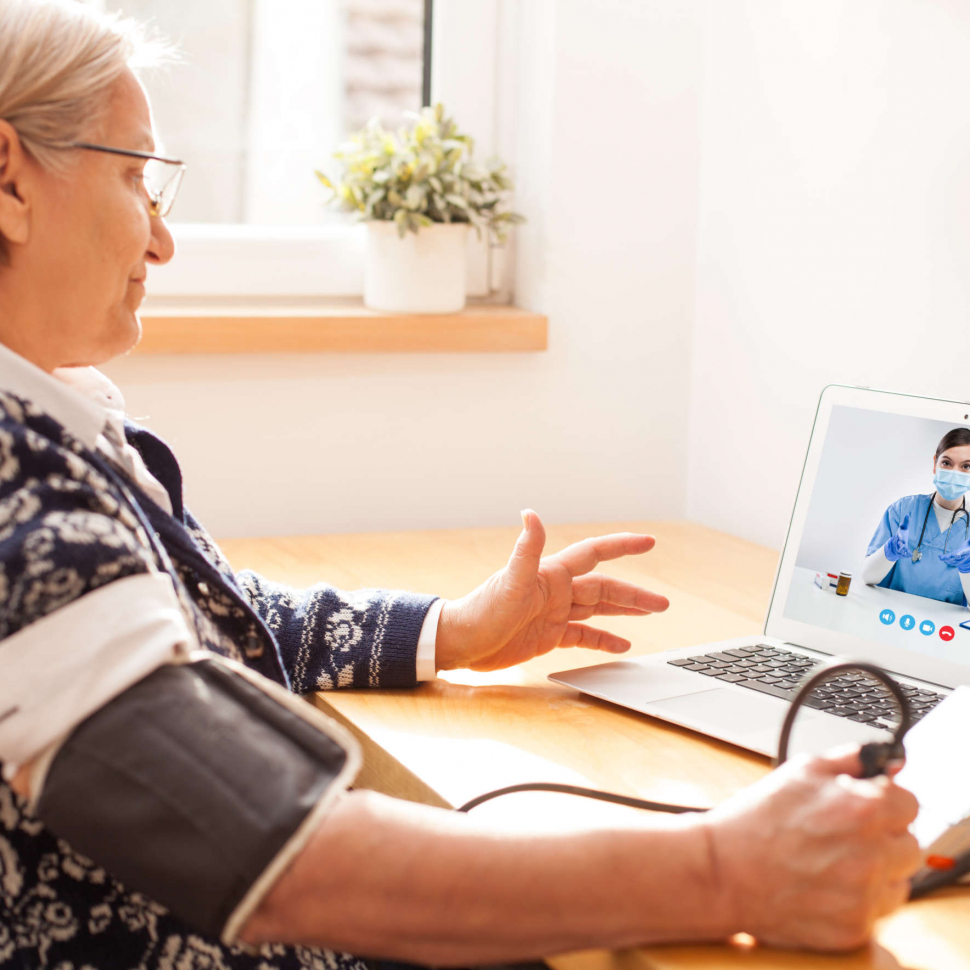 Elderly senior retired woman using sphygmomanometer blood pressure monitor to measure heart rate pulse,talking to female e-doctor via online video call help line,self-monitoring remote telemedicine